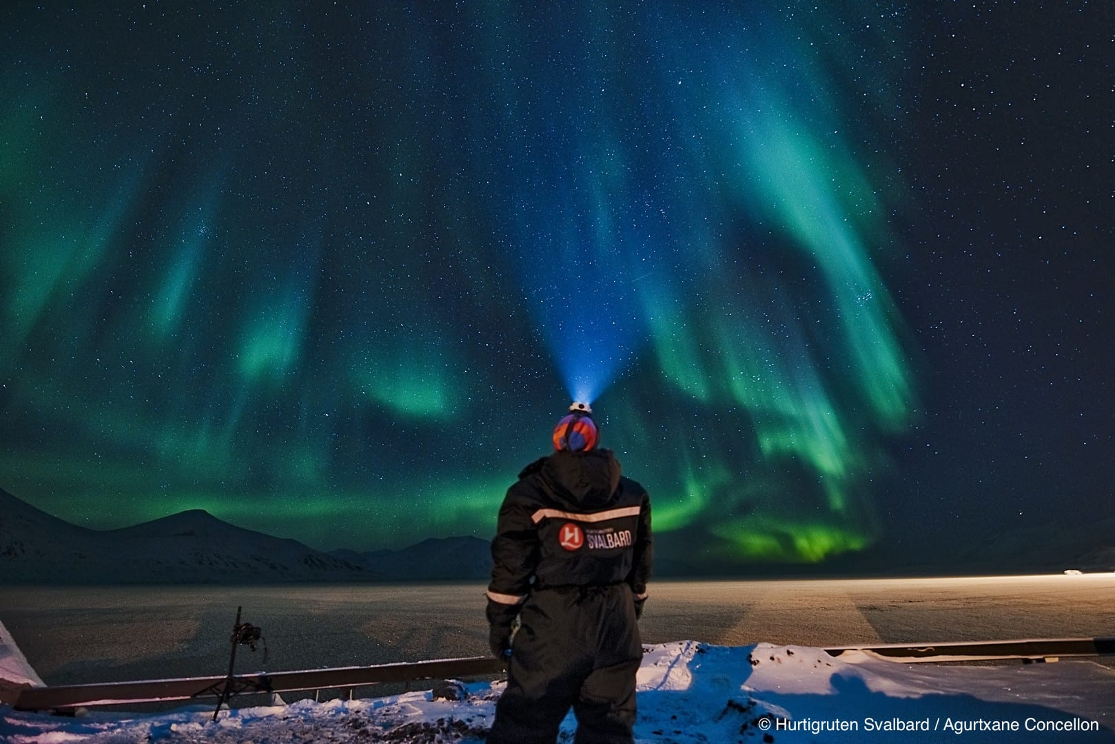 Man with back facing camera and visible Hurtigruten Svalbard suit looking up at green northern lights show in starry night sky with head torch in winter in Svalbard, Arctic Norway