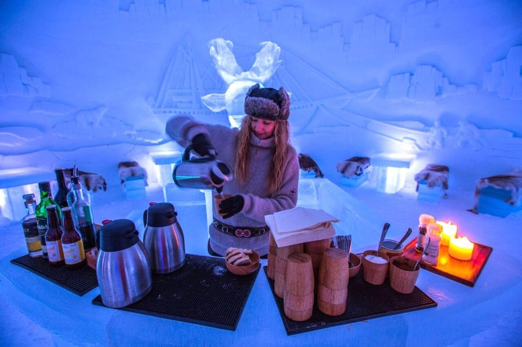 Norwegian girl pouring hot drinks behind ice bar at Ice Domes, Tromso, Norway