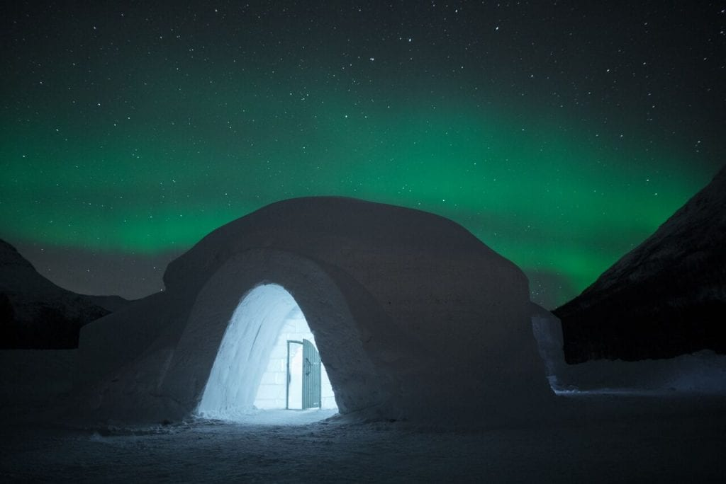 Ice dome exterior with view of lit up entrance and door in front of starry night sky and green northern lights in Arctic Norway