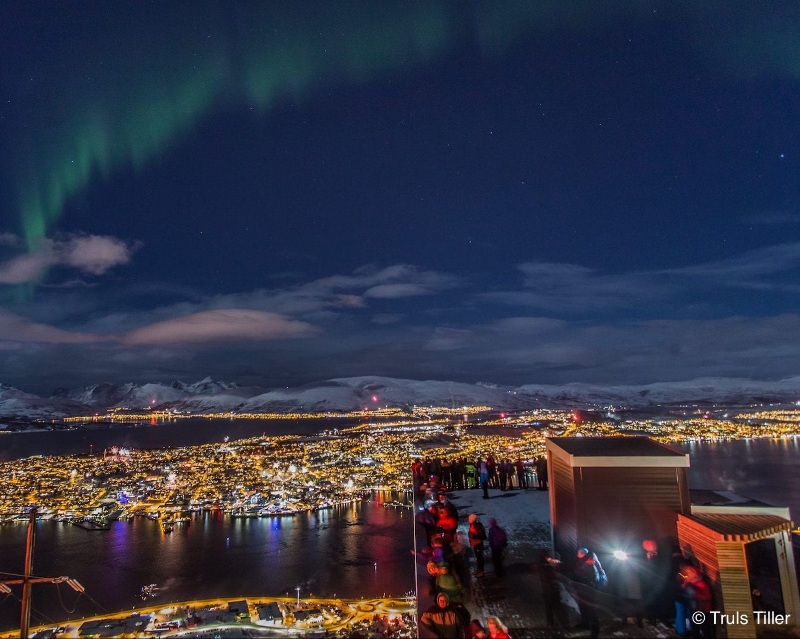 Northern Lights above panoramic view of Tromsø lit up with city lights From Fjellheisen Cable Car lookout point in Tromsø, Arctic Norway