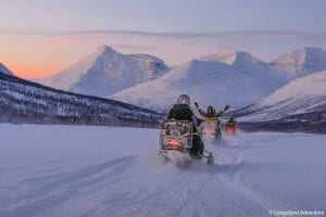 Three snowmobiles driving away from camera towards snowy winter mountains coloured purple by the sunset in Lyngen, Arctic Norway