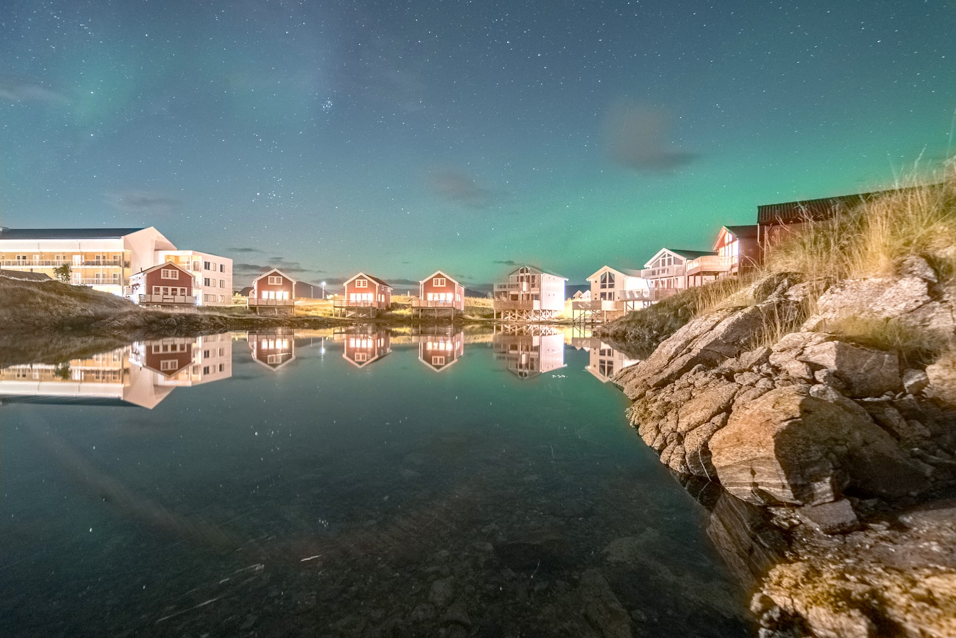 Water reflection of Northern Lights over Sommarøy Arctic Hotel building near Tromsø, Arctic Norway