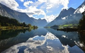 norway in a nutshell clear water fjords white clouds blue sky green nature light