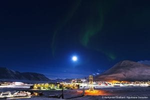 Northern Lights in darky sky above town of Longyearbyen in winter in Svalbard, Arctic Norway