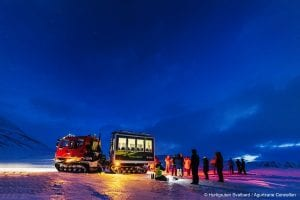 Snowcat with guide and people waiting outide behind it in dark blue winter landscape of Svalbard, Arctic Norway