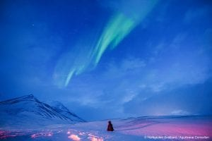 Person sitting on pink snowy ground in distance with back facing camera looking up at light northern lights show in light blue cloudy sky in Svalbard, Arctic Norway