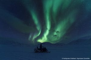 Person driving snowmobile to the right under a light green northern lights show in starry winter night sky in Svalbard, Arctic Norway