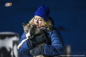 Blonde girl with dark blue beanie hat and puffer jacket holding sled dog puppy in Svalbard, Arctic Norway