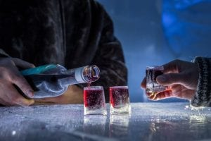 Close up of dark red shots being poured into ice shot glasses at ice bar in Arctic Norway