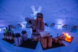 Girl with puffer hat serving drinks and bread behind ice bar in ice domes of Arctic Norway