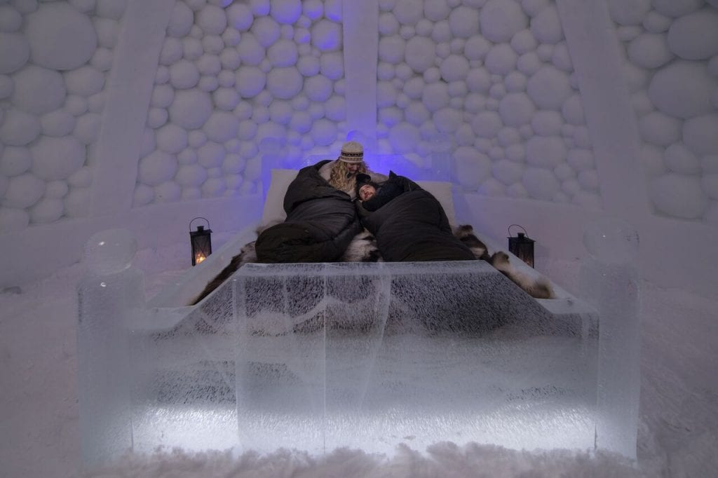 Couple cuddling in sleeping bags on reindeer skins on ice bed in ice hotel room of ice domes in Arctic Norway