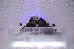 Couple cuddles in sleeping bags on an ice bed at Tromso Ice Domes in Arctic Norway
