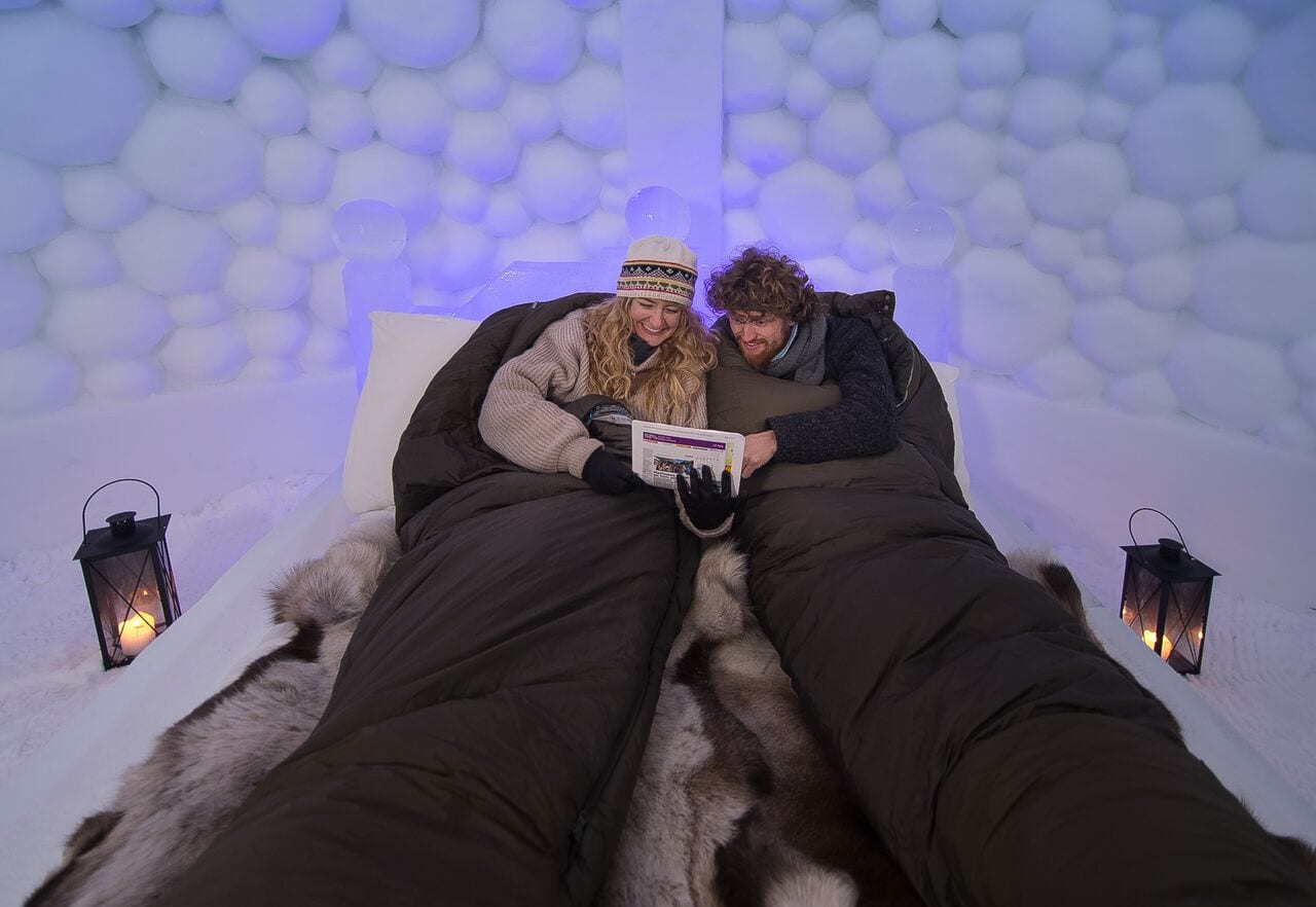 Couple reading in sleeping bags on ice bed with reindeer skins at Tromso Ice Domes in Arctic Norway