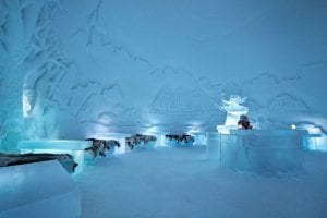 Ice dome bar and dining area with tables and reindeer skin covered seats and ice bar with reindeer sculpture in Arctic Norway