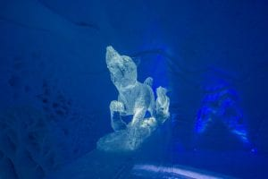 Ice dog sculpture facing forward with dark blue background inside ice domes in Arctic Norway