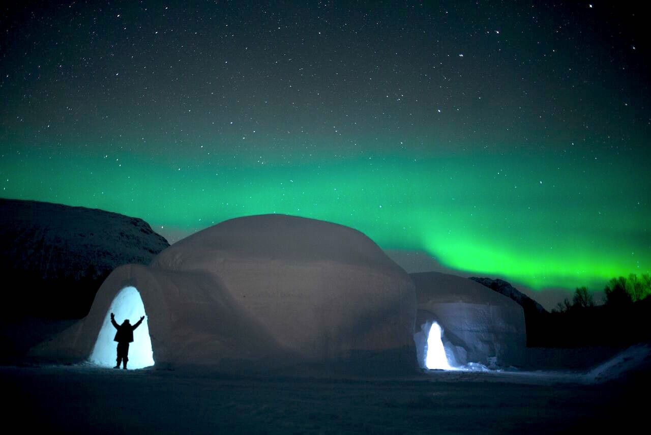 Ice domes with the silhouette of a person holding arms up at the entrance on a starry winter night with bright green northern lights in Arctic Norway
