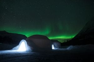 Ice dome exterior with view of lit up entrance in front of starry black night sky and bright green northern lights in Arctic Norway