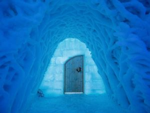 Blue ice tunnel leading to wooden door with reindeer antler handle at ice domes in Arctic Norway