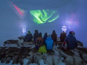 People sitting on reindeer skins in ice room with backs turned watching screening of northern lights video in ice domes of Arctic Norway