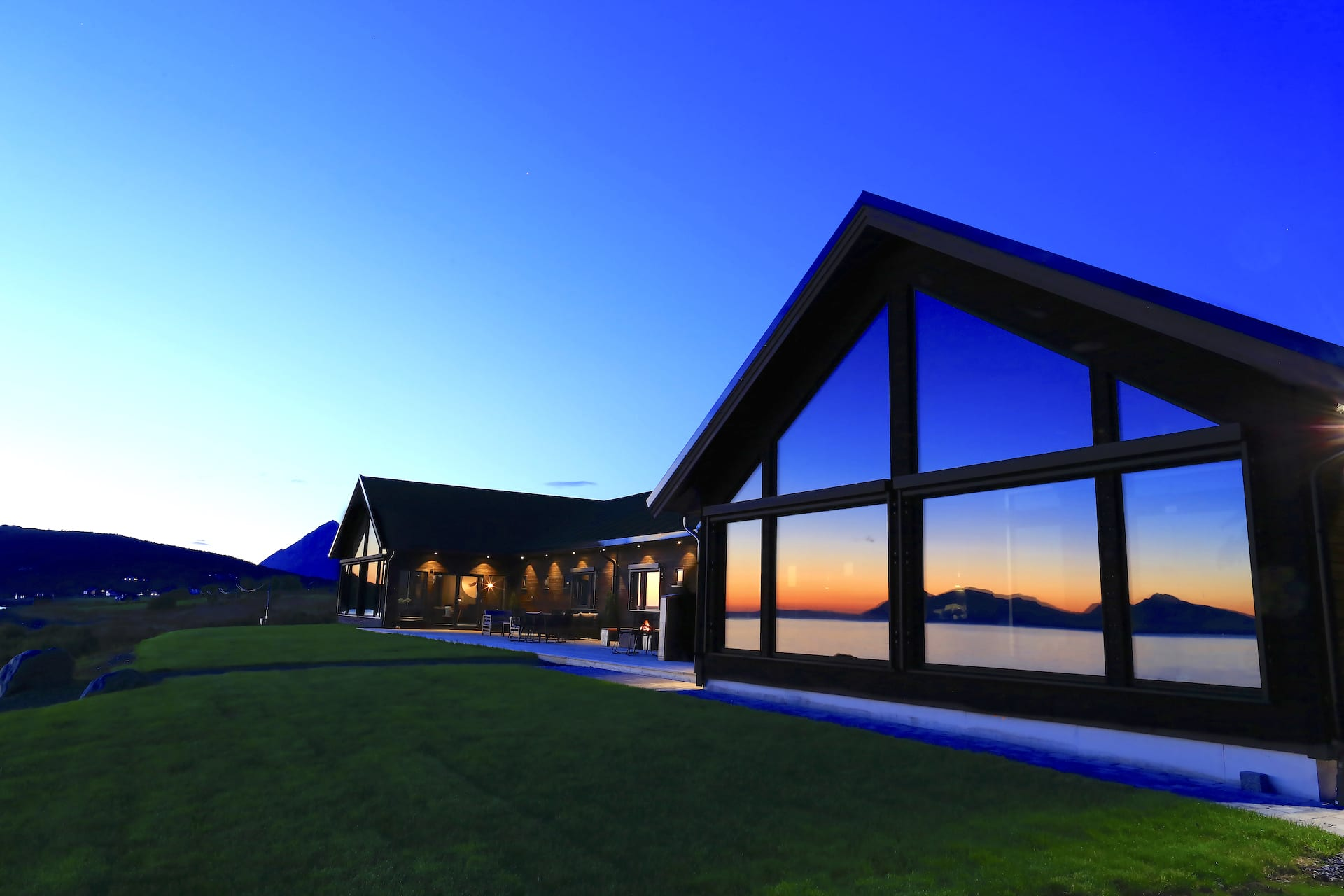 Exterior view of Lyngen Experience Lodge at sunset in summer with sea reflected off building window