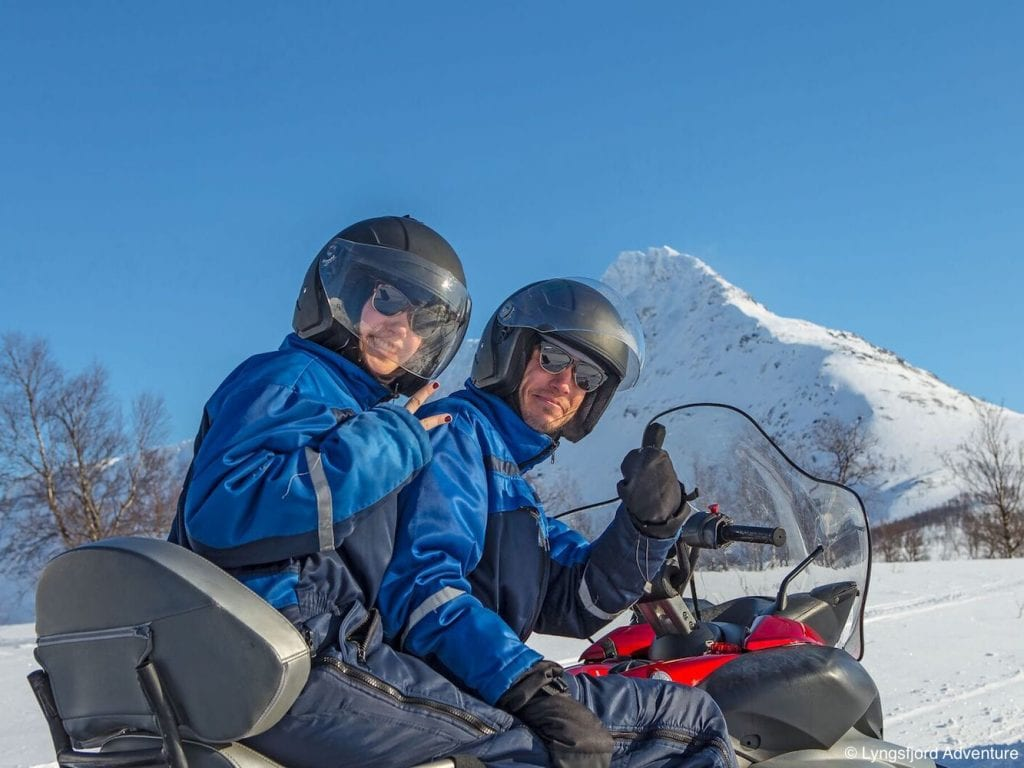 Couple on snowmobile smiling back at camera with shades and helmets giving peace sign and thumbs up in the mountains of Lyngen, Arctic Norway