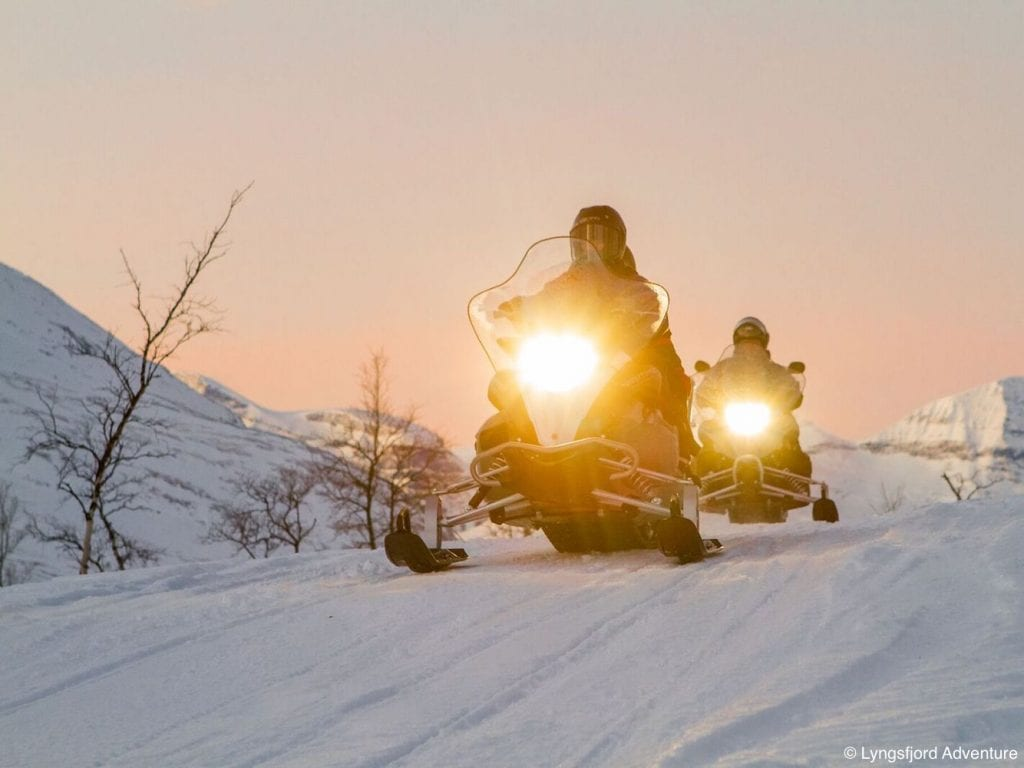 Two snowmobiles with lights on driving towards camera in front of pink winter sky in Lyngen, Arctic Norway