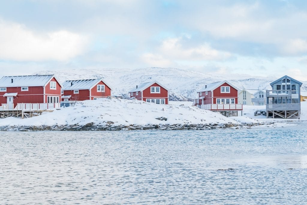 Snowy clear winter view of Sommaroy waterfront cabins outside Tromso, Norway.