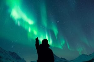 silhouette of person pointing at northern lights in tromso