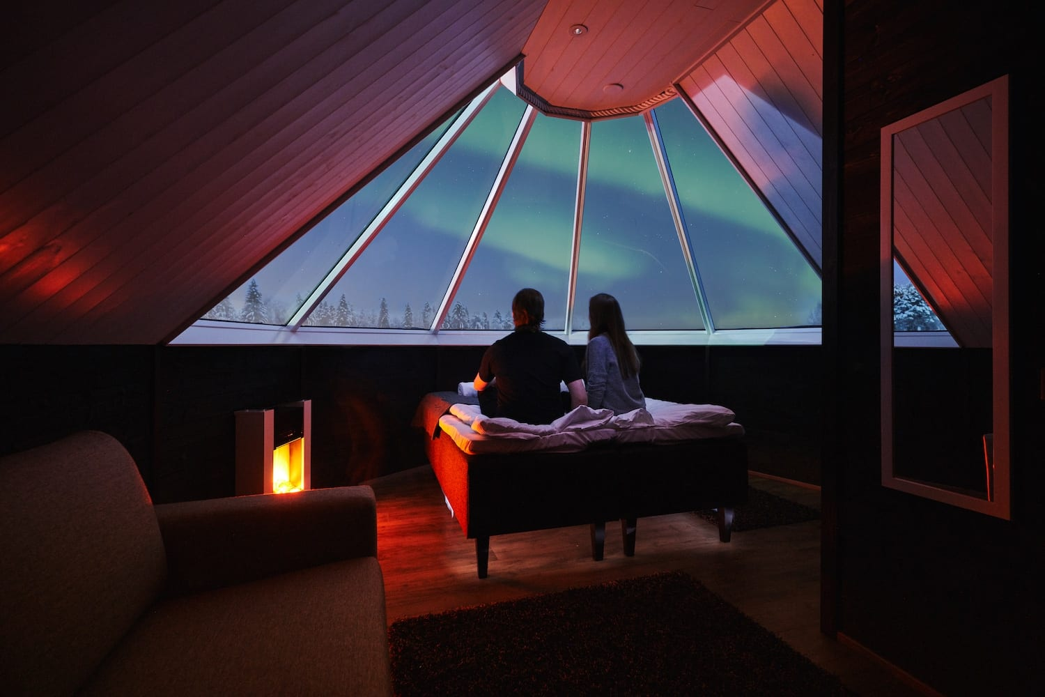 Couple sitting on bed in cosy aurora cabin looking out glass window at northern lights