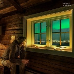 Man sitting in fishermen rorbuer cabin at night looking out of window at northern lights in svolvær, norway