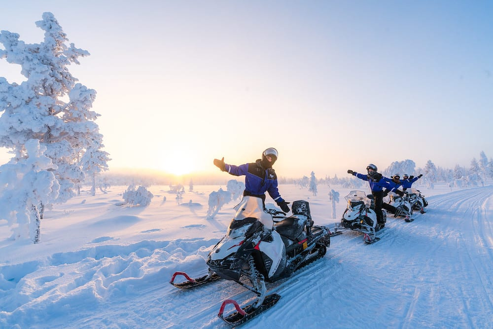 People on top of snowmobiles posing for photograph with snow covered trees and snow on ground with sun shining bright