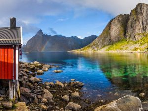 Eliassen Rorbuer in Lofoten Islands Norway with rainbow and mountain fjords and sea of water with rocks and red cabin
