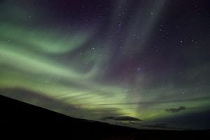 Northern Lights Aurora Borealis Nordurljos with stars in the sky and clouds