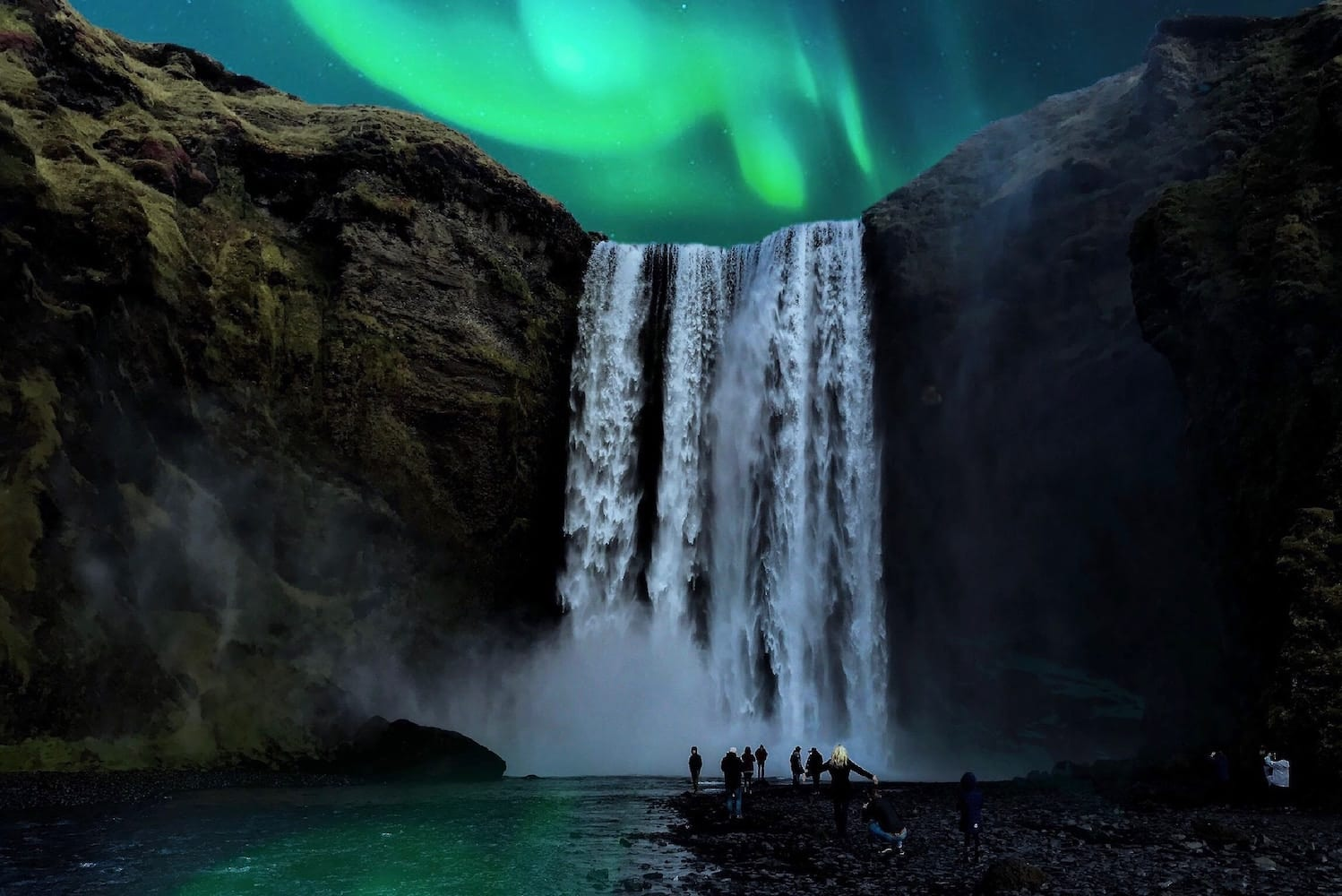 Northern Lights Aurora Borealis waterfall at night with people watching and taking photographs