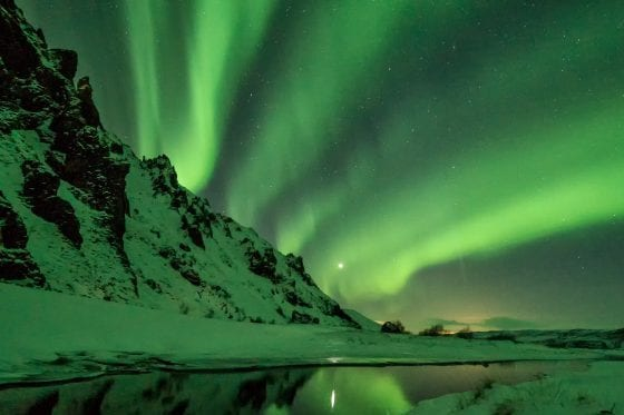 Northern Lights Aurora Borealis with snow coveredm ountains and sea of water