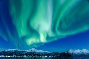 Northern Lights Aurora Borealis in the sky with snow covered fjords and trees with sea